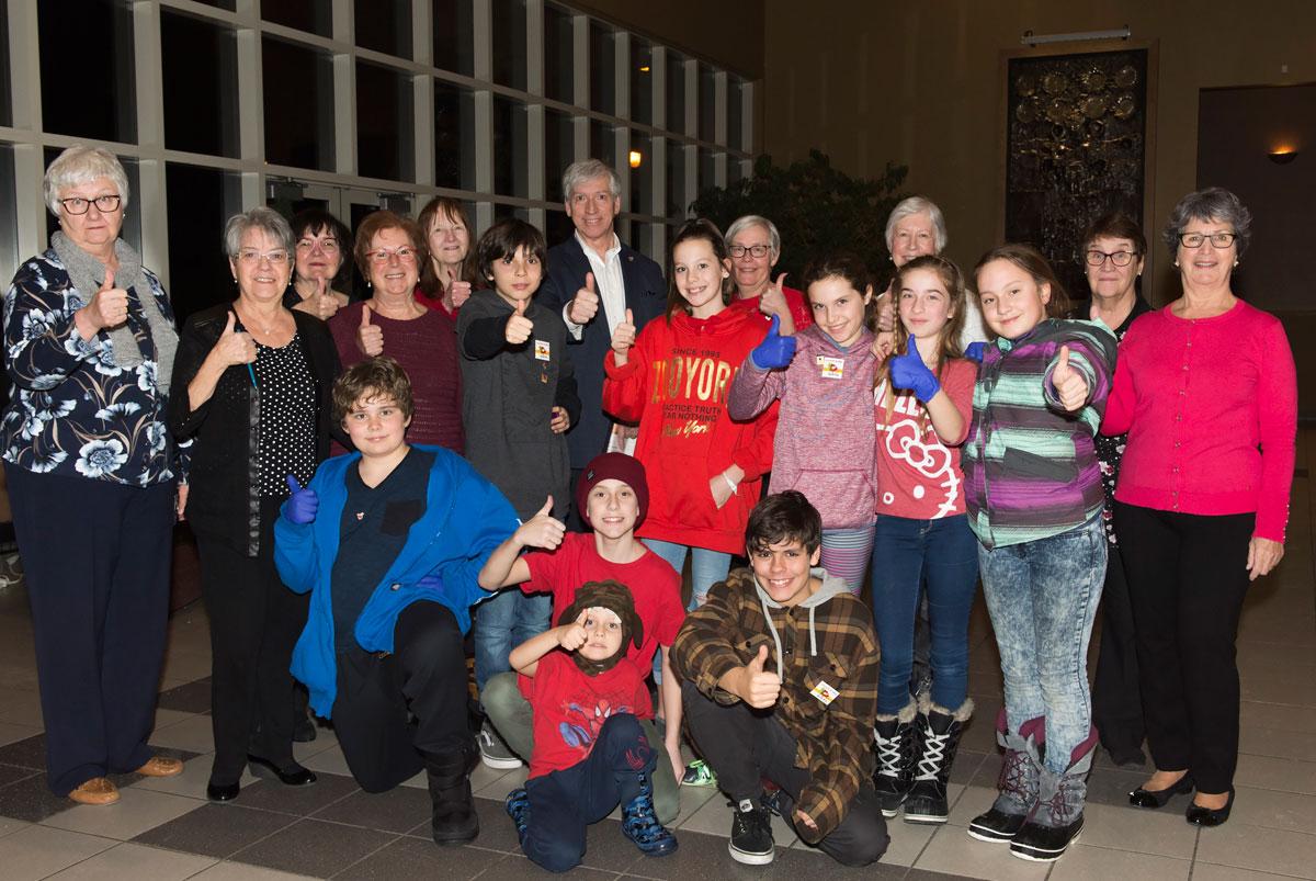 Le maire, monsieur Martin Murray, est entouré des bénévoles du Cercle de Fermières Saint-Bruno-de-Montarville et d'élèves de 6e année de l'école Albert-Schweitzer (groupe du soir).